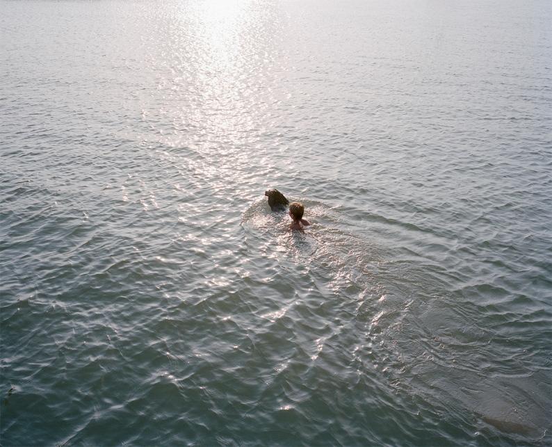 Un jeune garçon joue avec son chien à l'embouchure du Rhône.